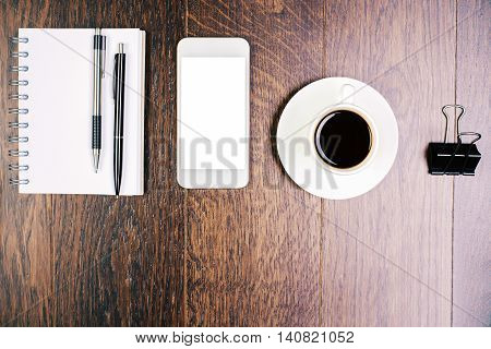 Top view of wooden office desktop with spiral notepad other stationery items blank white smartphone and coffee cup. Mock up
