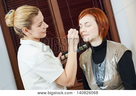 Makeup specialist applying mascara to woman eyelashes in beauty salon
