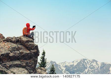successful backpacker taking photo on mountain peak