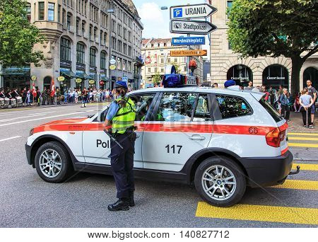 Zurich, Switzerland - 1 August, 2016: a policewoman watching the parade devoted to the Swiss National Day. The Swiss National Day is the national holiday of Switzerland set on 1 August.
