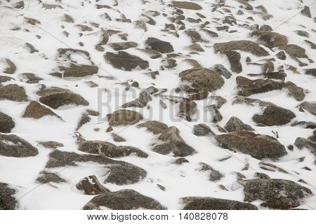 Large granite rocks partially covered by snow and ice in overcast, hazy weather