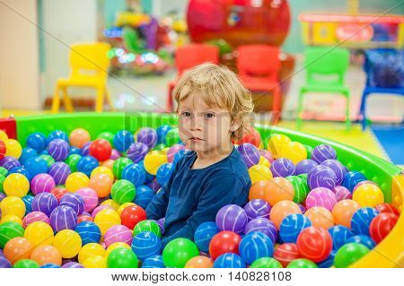 Boy Sits In The Balls In The Game Room