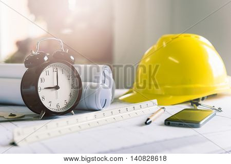 Morning time it's nine o'clock already A retro clock showing 9:00 am on the desk of engineer designer and architect in an office with equipment and drawing paper for working plan.