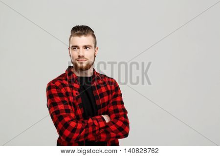 Young handsome man posing, arms crossed over grey background. Copy space.