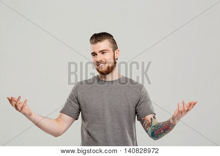 Young handsome man gesturing, smiling over grey background. Copy space.
