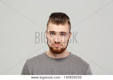 Upset young handsome man posing, looking at camera over grey background. Copy space.