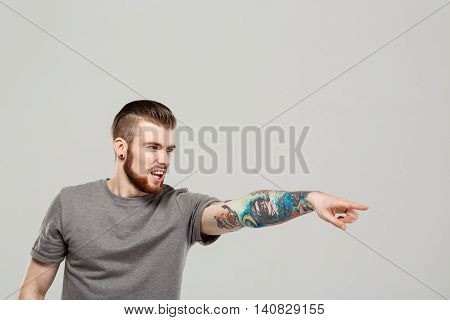Young handsome man pointing finger in side, shouting over grey background. Copy space.