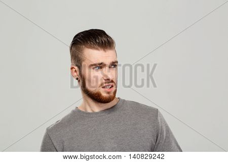 Upset young handsome man posing, looking aside over grey background. Copy space.