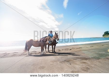 Te Kaha, New Zealand - January 13, 2013; Local riding on beach with two horses stops and stands still for a photo with lens flare from left