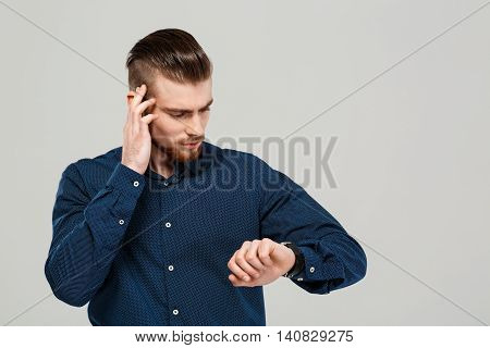 Young successful businessman looking at watch over grey background. Copy space.