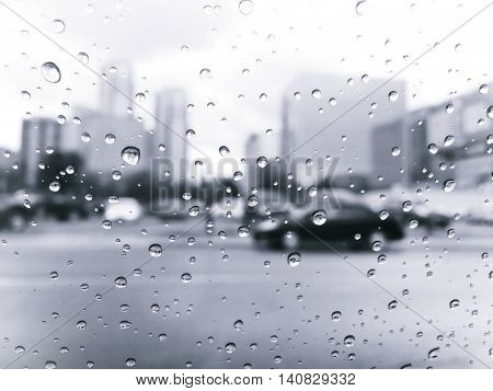 raindrops on car window in the city retro black and white style