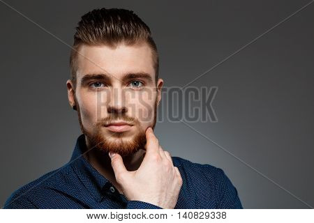 Young successful businessman posing, looking at camera over dark background. Copy space.
