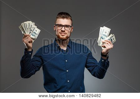 Young successful businessman in glasses smiling, looking at camera, holding money over dark background. Copy space.