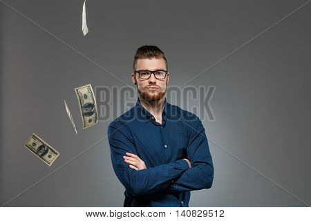 Young successful businessman in glasses looking at camera, posing among falling money over dark background. Copy space.