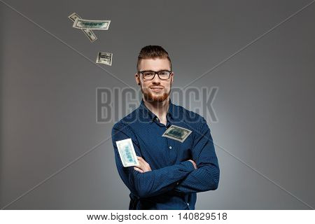 Young successful businessman in glasses smiling, looking at camera, posing among falling money over dark background. Copy space.