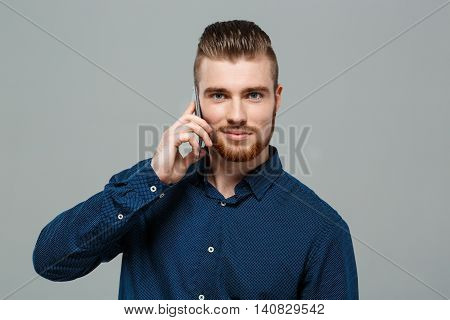 Young successful businessman smiling, looking at camera, speaking on phone over grey background. Copy space.