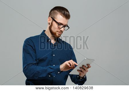 Young successful businessman in glasses looking at tablet over grey background. Copy space.