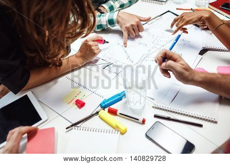 Close up photo of people's hands on business papers.