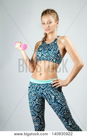 Image of fitness woman in sports clothing. Young sports sexy fitness woman body with dumbbells