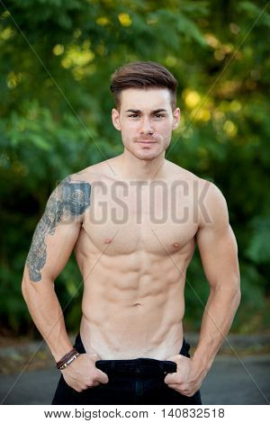 Handsome fit athletic shirtless young man against green nature
