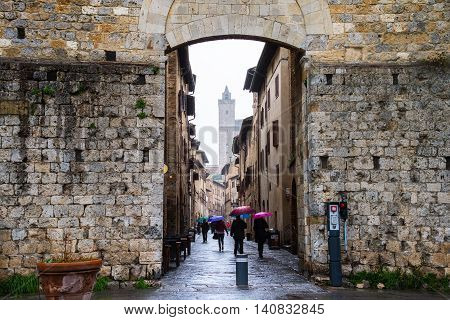 Unidentified people holding umbrellas and walking by the streets of old town San Gimignano in Siena, Italy