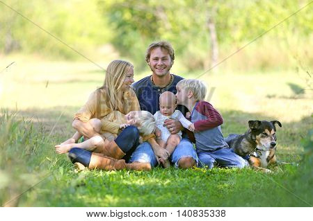 A happy family of five people including mother father new baby boy and his brother are sitting outside in the sunny garden with their adopted German Shepherd dog. Brother is kissing baby sister.
