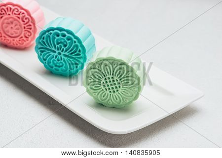 Sweet color of snow skin mooncake on plate. Chinese mid autumn festival foods. Traditional mooncakes on table