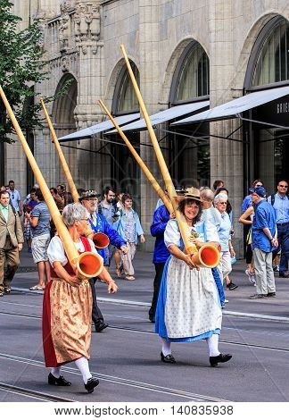Zurich, Switzerland - 1 August, 2016: participants of the parade devoted to the Swiss National Day passing along Bahnhofstrasse street. The Swiss National Day is the national holiday of Switzerland, set on 1 August.