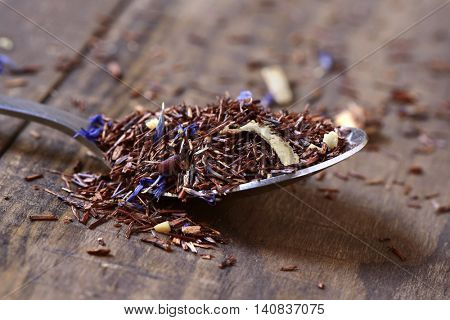 closeup of a spoon with rooibos tea mixed with flowers, dry fruits and herbs, on a rustic wooden table
