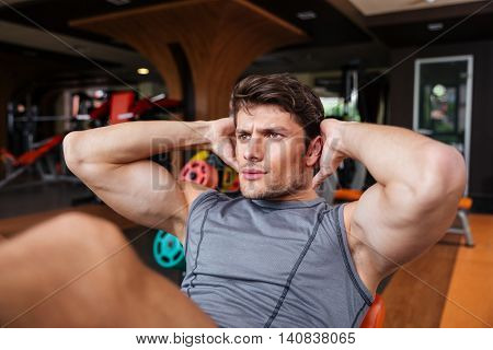 Close up portrait of a young handsome sports man doing press workout at the gym