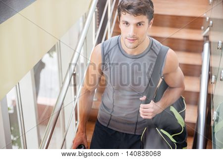 Handsome young sportsman with bag walking on training in gym