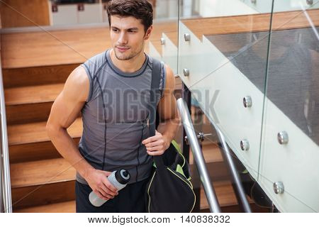 Portrait of attractive young man athlete with bag and bottle of water