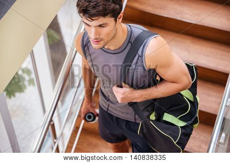 Attractive young fitness man with bag walking on stairs in gym