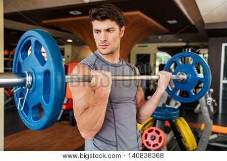 Handsome young man athlete working out with barbell in gym
