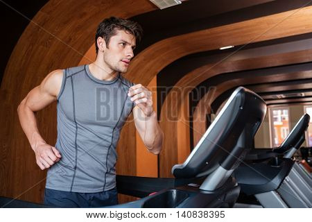Confident young man athlete running on treadmill in gym