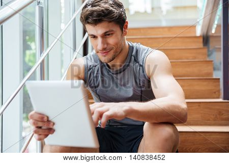 Attractive young man athlete sitting and using tablet in fitness club