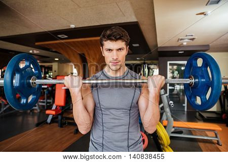 Portrait of attracitve young sportsman training using barbell in gym