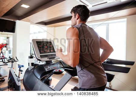 Back view of young sportsman working out and running on treadmill in gym
