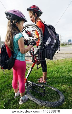 Bikes bicyclist girl. Children girls wearing bicycle helmet with hand pump for bicycle. Girl pump up bicycle tire. Children bicycle repair. Accident on summer road.
