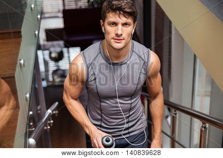 Sports man holding bottle with water and looking at camera at the gym