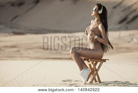 perfect sexy naked brunette woman in headphones on sand. Long black hair and red lips. Summer photo.
