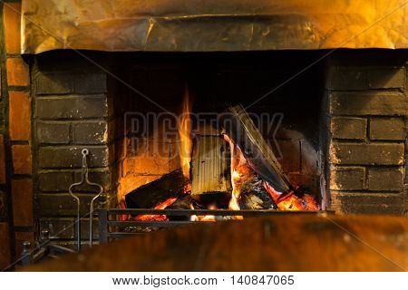 stove heating and fire concept - close up of burning fireplace at home