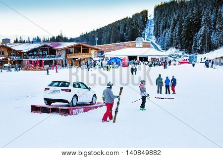 Bansko, Bulgaria - December, 12, 2015: Bunderishka polyana, restaurant, cafe, ski lift, mountains panorama with pine trees, people at Bansko ski resort