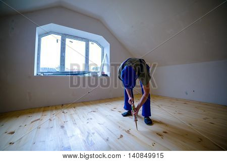 Wooden floor varnished. Worker with silicon gun.