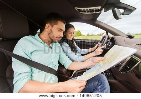 leisure, road trip, travel and people concept - happy man and woman driving in car and searching location on map