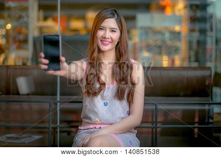 The Young Girl Holding A Remote Control Watching  Movie On Tv.