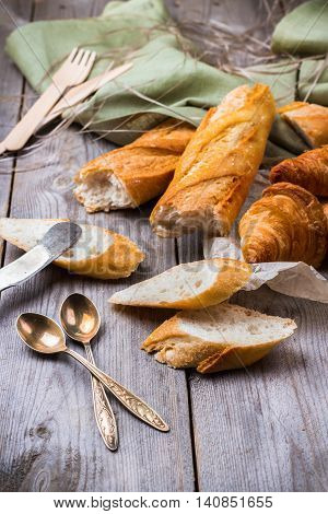 Still life, food and drink concept. French baguette with butter and croissant for breakfast on a rustic wooden table. Selective focus