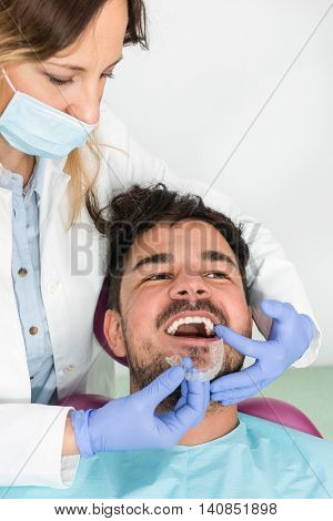 Young man getting dental braces, toned image