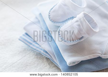 clothing, babyhood, motherhood and object concept - close up of baby bootees on pile of folded clothes for newborn boy
