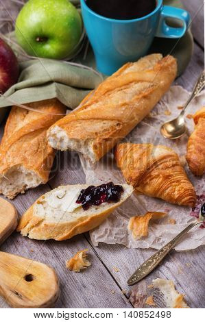 Still life, food and drink concept. French baguette with butter and jam, croissant, coffee for breakfast on a rustic wooden table. Selective focus